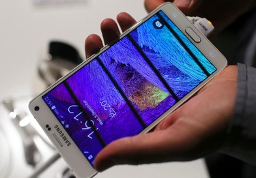 A visitor holds a new Samsung Galaxy Note Edge smartphone after its presentation at the Unpacked 2014 Episode 2 event ahead of the IFA Electronics show in Berlin, Sept. 3, 2014.  REUTERS/Hannibal Hanschke