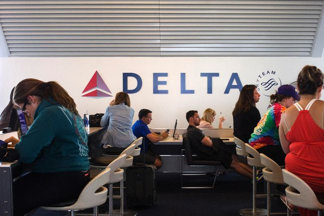 Passengers sit in stations equipped with iPads ahead of their flights at a Delta terminal in LaGuardia Airport in New York June 22, 2014. Picture taken June 22, 2014. (REUTERS/Adrees Latif)