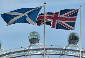 The Scottish saltire flag (L) and Union flag fly outside the Scottish Office, in central London.  REUTERS/Toby Melville