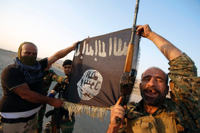 Iraqi Shiite militia fighters hold the Islamic State flag as they celebrate after breaking the siege of Amerli by Islamic State militants, September 1, 2014.  REUTERS/Youssef Boudlal