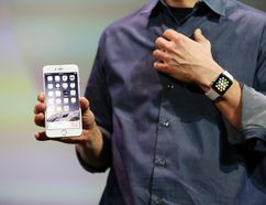 Apple CEO Tim Cook wears the Apple Watch and shows the iPhone 6 Plus during an Apple event at the Flint Center in Cupertino, California, September 9, 2014. (REUTERS/Stephen Lam)