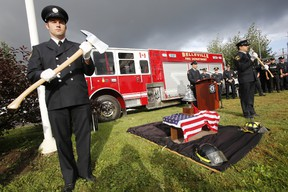 Belleville, Ont. firefighters Kyle Christopher, left, and Steve Morgan, right, stand by a piece of rusted, burned, scarred steel from the World Trade Centre on display alongside a fire bell and a pair of fire helmets as their colleague Steven Cowey, centre, speaks during a 9/11 memorial service at Station 1 on Moira Street West Thursday, Sept. 11, 2014. - JEROME LESSARD/THE INTELLIGENCER/QMI AGENCY