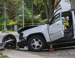 Belleville Police Const. Brad Stitt measures the scene on Dufferin Avenue north of Victoria Avenue in Belleville, Ont. after a northbound Chevrolet Trailblazer struck a tree Thursday, September 11, 2014. - Luke Hendry/The Intelligencer/QMI Agency