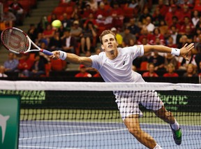 Vasek Pospisil of Canada dives for the ball during his Davis Cup world group men's doubles match with partner Daniel Nestor against Colombia's Juan-Sebastian Cabal and Robert Farah at the Metro Centre in Halifax on September 13, 2014. (REUTERS/Paul Darrow)