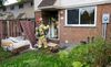 Firefighters talk at the back door of a townhouse at 1159 Huron St. following a morning fire at the London-Middlesex Housing Corp. complex in London on Sunday  CRAIG GLOVER/The London Free Press/QMI Agency