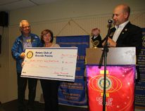 Rotary Club of Grande Prairie's Kevin Hilgers, right, talks about the Golden Harvest Youth Rehab Centre after he and fellow rotarian Vern Begalke,left, presented Greta Du Bois, president of the Rotary Club of Morningside in Johannesburg, South Africa with a $10,000 cheque to be used for a fitness centre at the facility during the local club's meeting on Friday. Jocelyn Turner/Daily Herald-Tribune