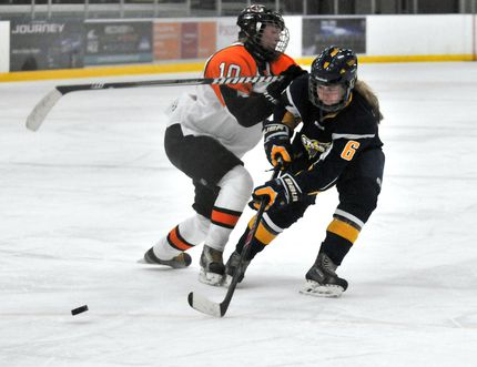 Tanel Boeckman, right, of the Nor-Lan Chrysler Female Midget AAA Storm, reaches for a loose puck as she's chekced by Taylor Stewart, left, of the Southeast Tigers, during the second game of the season at the Coca-Cola Centre on Sunday. The Storm defeated the Tigers 3-1 on Sept. 13 and 14. LOGAN CLOW /DAILY HERALD TRIBUNE