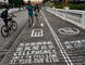 "A man rides his bicycle as people walk on the ""first mobile phone sidewalk in China"", which was recently installed at a tourism area in Chongqing municipality, September 13, 2014. The mobile phone sidewalk in Chongqing was divided into two sides -- one was written with ""Cellphones walk in this lane at your own risk"" while the other with ""No cellphones,"" as an attempt to reduce pedestrian incidents, local media reported. Picture taken September 13, 2014. REUTERS/China Daily"