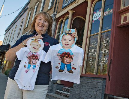 Jean Tucker, festival co-ordinator for St. George AppleFest, holds a couple of children's outfits which will be available at the annual festival on the weekend. (Brian Thompson, The Expositor)