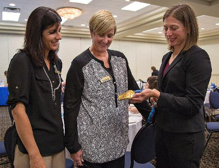 France Thibeault (left), branch manager at RBC Lynden Road, and Leslie Barker, program co-ordinator for the Chamber of Commerce Brantford-Brant, look at Becky Kellar-Duke's Olympic gold medal on Wednesday. Kellar-Duke was the keynote speaker at a Women In Business luncheon at the Best Western Brant Park Inn. (Brian Thompson, The Expositor)