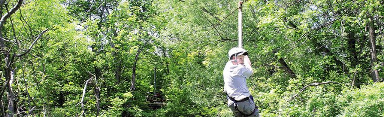 John Mifkovic, leader of the 74th Scout Pack, London, Ont., rides on a zip line at Camp Timken in this 2010 photo.