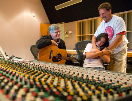 Songwriter, teacher and producer Steve Revington, left, shows Faith Abbey and her father, Dave, the soundboard used to record a collaborative song about Faith's arsenal used to beat liver cancer at the age of two, at EMAC Studios in London. Faith and her father completed a 96-km walk from London to Sarnia last week to raise money and awareness for C