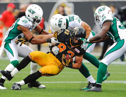 Hamilton Tiger-Cats' Andy Fantuz is stopped by Saskatchewan Roughriders' Weldon Brown, left, Chad Kilgore and Tristan Jackson during the Ticats' 28-3 win Sept. 14, 2014, in Hamilton. (MARK BLINCH/Reuters)