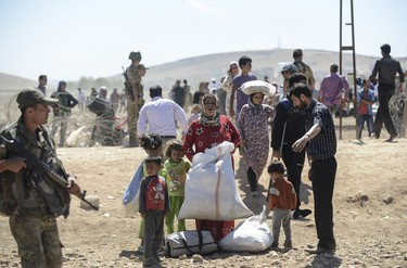 """Syrian Kurdish families lay their belongings on the ground after they crossed the border between Syria and Turkey near the southeastern town of Suruc in Sanliurfa province, on September 20, 2014. Several thousand Syrian Kurds began crossing into Turkey on September 19 fleeing Islamic State fighters who advanced into their villages, prompting warnings of massacres from Kurdish leaders. Turkey on September 19 reopened its border with Syria to Kurds fleeing Islamic State (IS) militants, saying a """"worst-case scenario"""" could drive as many as 100,000 more refugees into the country. AFP PHOTO/BULENT KILIC"""