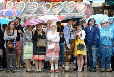 Visitors wait outside of festival tents for the opening of the traditional Bavarian Oktoberfest festival at the Theresienwiese in Munich, southern Germany, on September 20, 2014. Germany's world-famous Oktoberfest kicks off with millions of revellers set to soak up the frothy atmosphere in a 16-day extravaganza of lederhosen, oompah music and, of course, beer.  AFP PHOTO / CHRISTOF STACHE