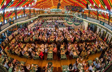 Visitors sit in the new Marstall festival tent during the opening of the traditional Bavarian Oktoberfest festival at the Theresienwiese in Munich, southern Germany, on September 20, 2014. Germany's world-famous Oktoberfest kicks off with millions of revellers set to soak up the frothy atmosphere in a 16-day extravaganza of lederhosen, oompah music and, of course, beer.  AFP PHOTO / DPA / MARC MILLER