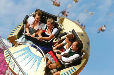 Visitors enjoy a firground ride during the opening day of the 181st Oktoberfest in Munich September 20, 2014. Millions of beer drinkers from around the world will come to the Bavarian capital over the next two weeks for the Oktoberfest, which starts today and runs until October 5.  REUTERS/Michael Dalder