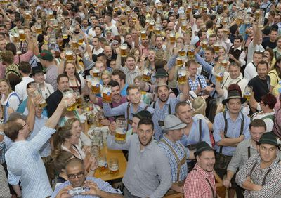 Visitors celebrate with first beer mugs the opening of the traditional Bavarian Oktoberfest festival at the Theresienwiese in Munich, southern Germany, on September 20, 2014. Germany's world-famous Oktoberfest kicks off with millions of revellers set to soak up the frothy atmosphere in a 16-day extravaganza of lederhosen, oompah music and, of course, beer.  AFP PHOTO / CHRISTOF STACHE