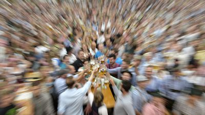 Zoomed in picture of visitors which celebrate with first beer mugs during the opening of the traditional Bavarian Oktoberfest festival at the Theresienwiese in Munich, southern Germany, on September 20, 2014. Germany's world-famous Oktoberfest kicks off with millions of revellers set to soak up the frothy atmosphere in a 16-day extravaganza of lederhosen, oompah music and, of course, beer.  AFP PHOTO / CHRISTOF STACHE