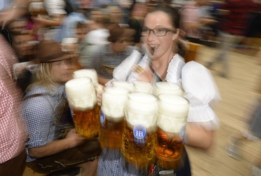 A waitress with a whistle serves beer mugs during the opening of the traditional Bavarian Oktoberfest festival at the Theresienwiese in Munich, southern Germany, on September 20, 2014. Germany's world-famous Oktoberfest kicks off with millions of revellers set to soak up the frothy atmosphere in a 16-day extravaganza of lederhosen, oompah music and, of course, beer.  AFP PHOTO / CHRISTOF STACHE