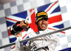 Lewis Hamilton sprays champagne on the podium following the Singapore F-1 Grand Prix at the Marina Bay street circuit in Singapore on Sunday. (Reuters)