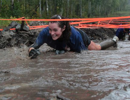 Valerie Malinowski crawls through a pit of mud and water during the inaugural Muddy Mountain Mixer obstacle course held at Kamiskotia Snow Resort on Saturday. The event drew 100 participants and raised money for the Canadian Cancer Society.