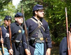 Re-enactors dressed as Union soldiers in the 42nd New York infantry walk toward their impending doom at the annual American Civil War re-enactment in Otterville on Sunday. BRUCE CHESSELL/Sentinel-Review