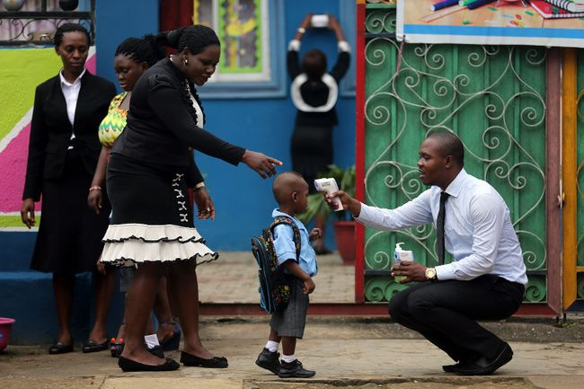 A school official takes a pupil's temperature using an infrared digital laser thermometer in front of the school premises, at the resumption of private schools, in Lagos on September 22, 2014. (REUTERS/Akintunde Akinleye)