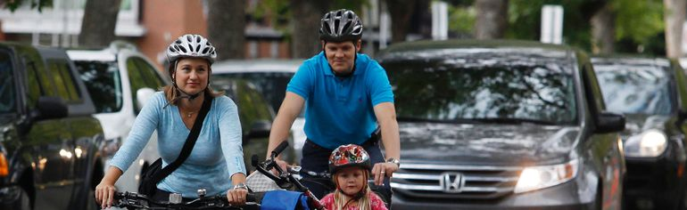 Julie and Brendan Kusiek ride along a temporary bike route on 83 Avenue with their three daughters on Sept. 19. Edmonton's sustainable transportation department unveiled Friday the city's newest bike routes along 83 and 102 Avenues. TREVOR ROBB QMI Agency