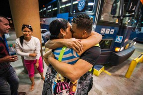 Cuban migrant Mailin Perez embraces with her husband Jose Caballero after arriving via Mexico at a bus station in Austin, Texas September 25, 2014.  Almost a year after he smuggled his way out of Cuba on a homemade boat, Caballero was reunited late Thursday with his wife who survived a harrowing sea voyage of her own last month.  REUTERS/Ashley Landis