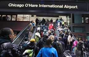 Crowds of travelers leave the subway at the Chicago O'Hare International Airport in this file photo taken November 23, 2011. All flights into and out of Chicago's O'Hare and Midway international airports were grounded early on Friday due to a fire at an air traffic control facility, the Federal Aviation Administration said.    REUTERS/Bob Strong/Files