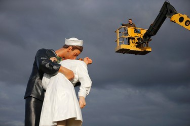 """A worker takes a picture of the """"Unconditional Surrender"""" sculpture by artist Seward Johnson of the U.S. during its installation outside the Memorial of Caen museum in Caen, September 25, 2014. The 25-foot statue of a sailor kissing a nurse is to spend a year in front of the Caen Memorial, a museum known for its extensive collection documenting the Normandy invasion in 1944 and World War II.   REUTERS/Stephane Mahe"""