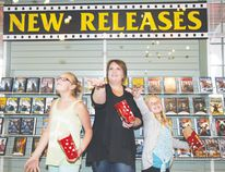 Melissa Ganske stands with her two daughters in front of new releases section at her movie rental store, Showtime. The store opened on Aug. 1 and Ganske offers popcorn, snacks and ice cream along with a wide selection of films.