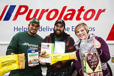 (From left) Matthew Morin, Colin Tinkler and Edith Inder pose with Food Bank donations for the Purolator Tackle Hunger Game prior to the Edmonton Eskimos' CFL football game against the Saskatchewan Roughriders at Commonwealth Stadium in Edmonton, Alta., on Friday, Sept. 26, 2014. Codie McLachlan/Edmonton Sun/QMI Agency