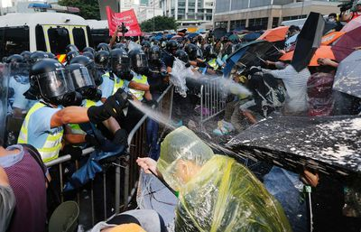 Riot policemen (L) use pepper spray during clash with protesters, as tens of thousands of protesters block the main street to the financial Central district outside the government headquarters in Hong Kong, September 28, 2014.  REUTERS/Tyrone Siu