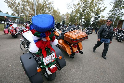 A biker checks out the toys attached to motorcycles at the end of the the 31th annual Edmonton Motorcycle Toy Run at Hawrelak Park in Edmonton, Alberta on September 28, 2014. Perry Mah/Edmonton Sun/QMI Agency