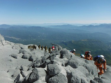 Firefighters and Japan Self-Defense Force soldiers climb up Mt. Ontake, which straddles Nagano and Gifu prefectures, central Japan, for a rescue operation, in this handout photograph released by Nagoya City Fire Bureau and taken September 28, 2014.     REUTERS/Nagoya City Fire Bureau/Handout via Reuters