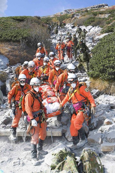 Firefighters carry a hiker during rescue operations on Mount Ontake, which straddles Nagano and Gifu prefectures, central Japan, in this handout photograph released by the Tokyo Fire Department and taken September 28, 2014. REUTERS/Tokyo Fire Department/Handout via Reuters
