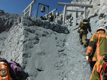 Japan Self-Defense Force soldiers and firefighters conduct rescue operations at mountain lodges, covered with volcanic ash as volcanic smoke rises near the peak of Mt. Ontake, which straddles Nagano and Gifu prefectures, central Japan, in this handout photograph released by Nagoya City Fire Bureau and taken September 28, 2014. REUTERS/Nagoya City Fire Bureau/Handout via Reuters