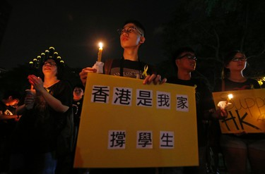 """People attend a candlelight vigil in solidarity with protesters of the """"Occupy Central"""" movement in Hong Kong, at Hong Lim Park Speakers' Corner in Singapore October 1, 2014. The sign reads, """"Hong Kong is my home, support student protesters."""" REUTERS/Edgar Su"""