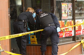 Forensics officers dust for fingerprints Thursday, Oct. 1, 2014 at a restaurant on Eglinton Ave. W., just west of Oakwood Ave., after a man was fatally stabbed and a woman wounded. (CHRIS DOUCETTE/TORONTO SUN)