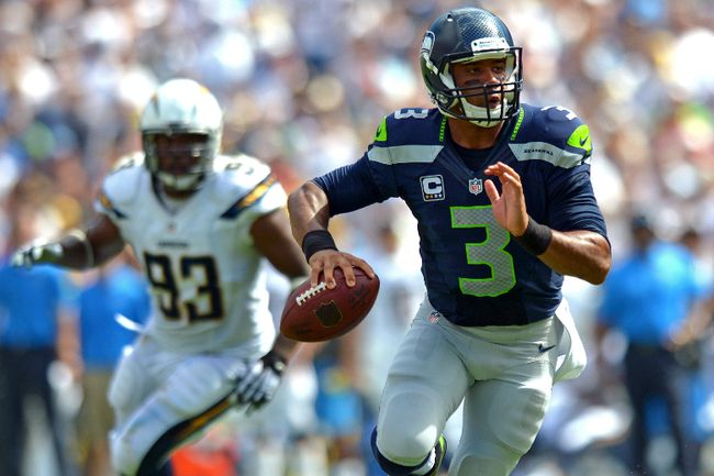 Seattle Seahawks quarterback Russell Wilson looks to pass as San Diego Chargers outside linebacker Dwight Freeney gives chase at Qualcomm Stadium on September 14, 2014. (Jake Roth/USA TODAY Sports)