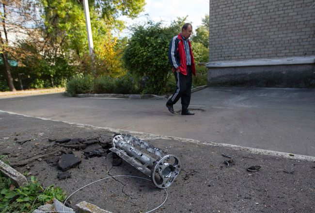 A man walks past a fragment of a missile launched from a Uragan multiple launcher system after recent shelling in Donetsk, eastern Ukraine, Oct. 5, 2014.