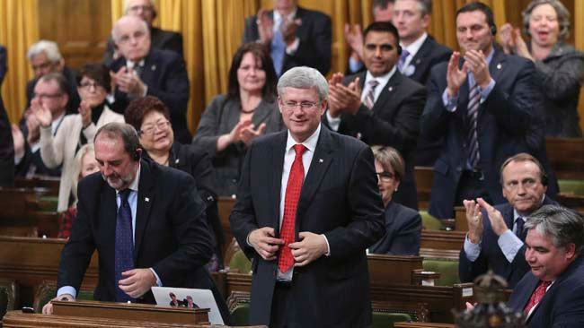 Prime Minister Stephen Harper stands to vote in favour of a government motion to participate in U.S.-led air strikes against Islamic State militants operating in Iraq, in the House of Commons on Parliament Hill in Ottawa October 7, 2014.  REUTERS/Chris Wattie