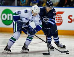 Vancouver Canucks' Hunter Shinkaruk battles for the puck against Jean Dupuy of the Winnipeg Jets during the 2014 Young Stars Classic Tournament in Penticton, B.C., on Sept. 14. (Al Charest/QMI Agency)