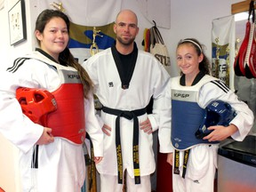 Danielle Ennett (left), head instructor Mark Warburton and Chloe Pretty stand in Petrolia Taekwondo. Ennett and Pretty are both ranked as top martial artists in the province heading into the Ontario team trials. BRENT BOLES/ QMI Agency