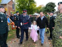 Sophie Voss, 7, is led from her backyard after her new playground was unveiled in Tara on Friday. The Make-A-Wish event included the royal treatment for the little girl, including a parade down Tara's main street and a celebration with more than 1,000 people at the community centre. Sophie is in remission after being diagnosed with acute lymphoblastic leukemia almost two years ago. (James Masters The Sun Times)