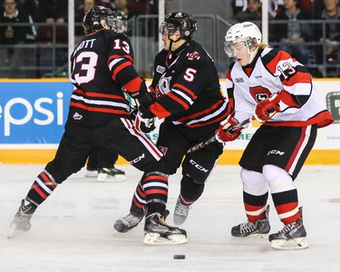 Ottawa 67's Artur Tyanulin works the puck past Niagara IceDogs Blake Siebenaler (#5) and Graham Knott during OHL hockey action at TD Place on Friday October 10, 2014. Errol McGihon/Ottawa Sun/QMI Agency
