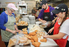 Loretta Jarrell, left, Antonio Cillero and Jodie Martin, just three of many volunteers at Martha's Table, help prepare the dressing and vegetarian option as part of a Thanksgiving meal at the centre in 2016. Martha's Table serves more than 230 free Thanksgiving meals each year. (Julia McKay/The Whig-Standard)