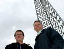 Hank Wall of VISP and Conley Kehler of MCI in Gretna stand on the school roof next to the tower that supplies VISP throughout Gretna. (LORI PENNER/Red River Valley Echo)
